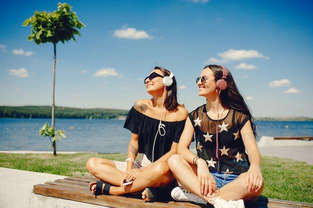 Modieuze meisjes die in een de zomerpark lopen Gratis Foto