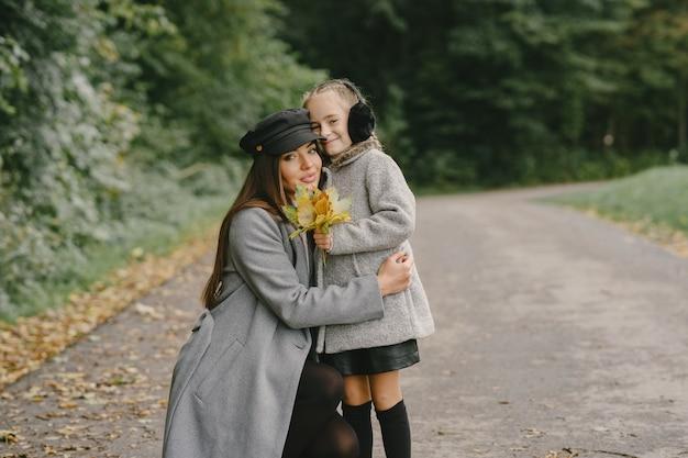 Modieuze moeder met dochter. mensen lopen naar buiten. vrouw in een grijze jas. Gratis Foto