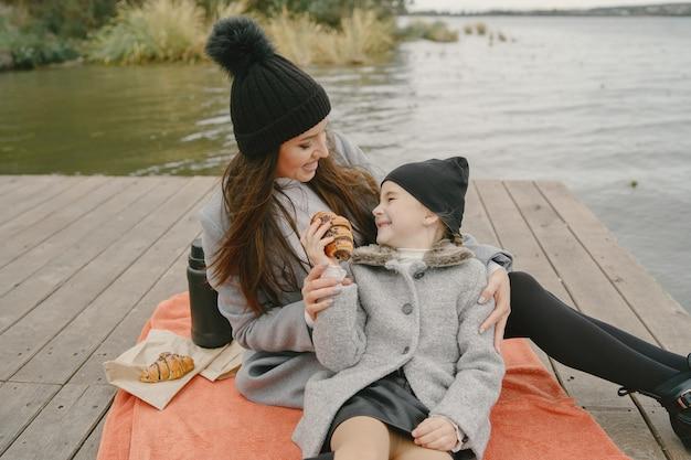 Modieuze moeder met dochter. mensen op een picknick. vrouw in een grijze jas. familie aan het water. Gratis Foto