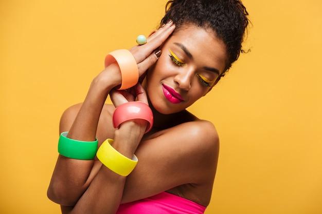 Modieuze mooie afrikaanse amerikaanse vrouw met heldere make-up die veelkleurige juwelenholdingshanden tonen bij gezicht, over geel wordt geïsoleerd die Gratis Foto