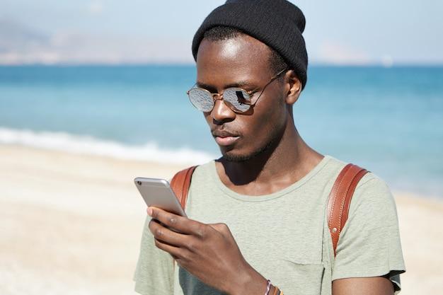 Modieuze serieuze afrikaanse man-backpacker die foto's plaatst via sociale media, met behulp van een 3g- of 4g-internetverbinding op een mobiele telefoon terwijl hij de wereld rondreist, blauwe oceaan en lucht in de horizon Gratis Foto
