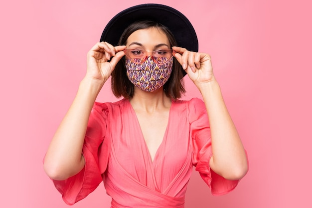Modieuze vrouw gekleed beschermend stijlvol gezichtsmasker. zwarte hoed en zonnebril dragen. poseren over roze muur Gratis Foto