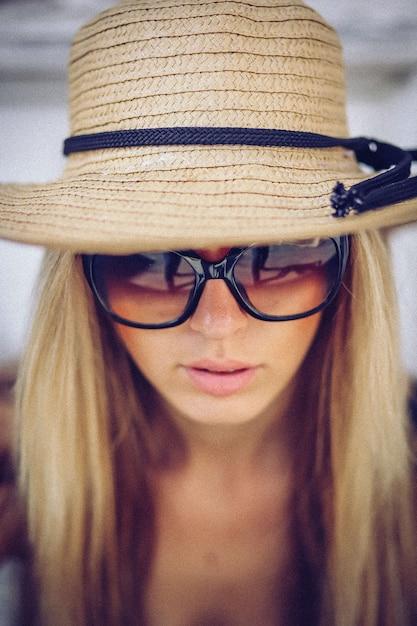 Modieuze vrouw in witte hoed die zich op oude stad bevindt Premium Foto