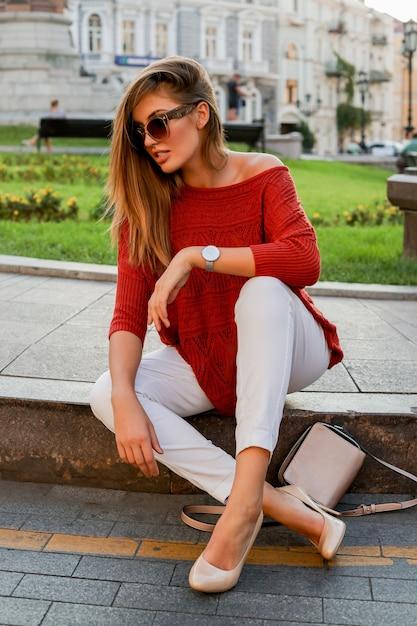 Modieuze witte vrouw in trui zittend op straat in het centrum. stijlvolle zonnebril. herfststemming. Gratis Foto