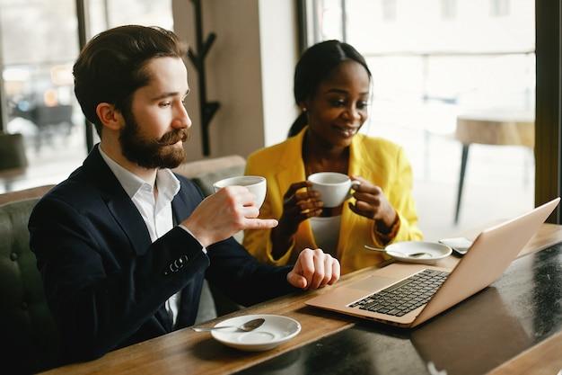 Modieuze zakenman die in een bureau met partner werkt Gratis Foto