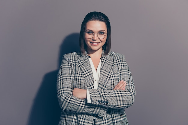 Modieuze zakenvrouw draagt een geruite blazer poseren binnenshuis Premium Foto