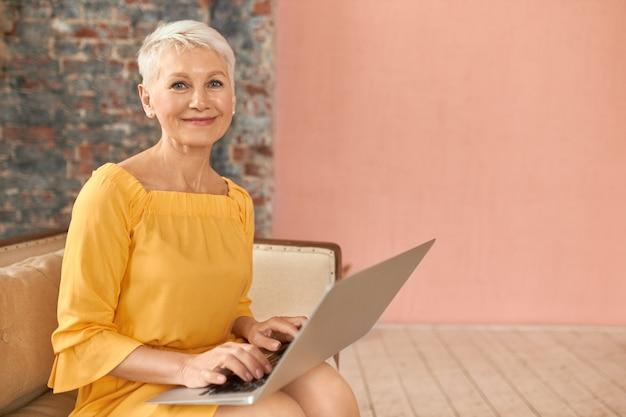 Modieuze zakenvrouw van middelbare leeftijd die e-mail controleert, zittend op de bank met een draagbare computer op haar schoot, toetsen, met behulp van draadloze high-speed internetverbinding thuis. mensen, leeftijd en technologie Gratis Foto