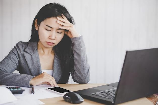 Moe aziatische zakenvrouw ongelukkig werken Premium Foto
