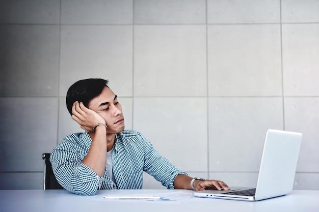 Moe en beklemtoonde jonge zakenmanzitting op bureau in bureau met computer Premium Foto