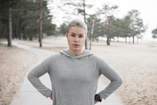 Moe fit slank meisje in hoodie poseren buitenshuis, handen houden op haar taille en camera kijken, rust hebben tijdens cardio-running training. mensen, levensstijl, activiteit, gezondheid en fitnessconcept Gratis Foto