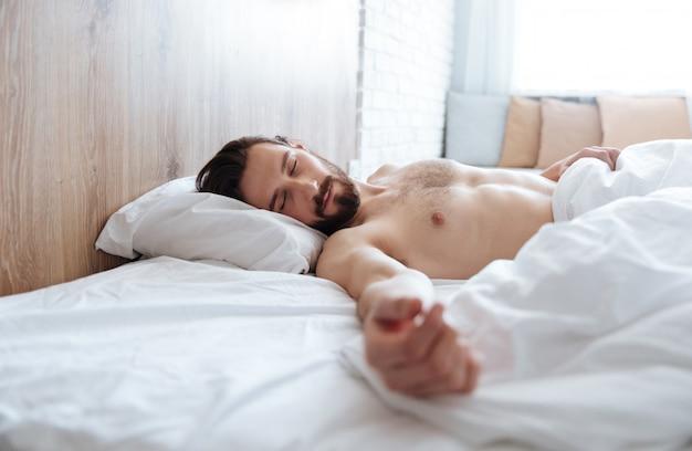 Moe vermoeid jonge man liggen en slapen in bed Gratis Foto