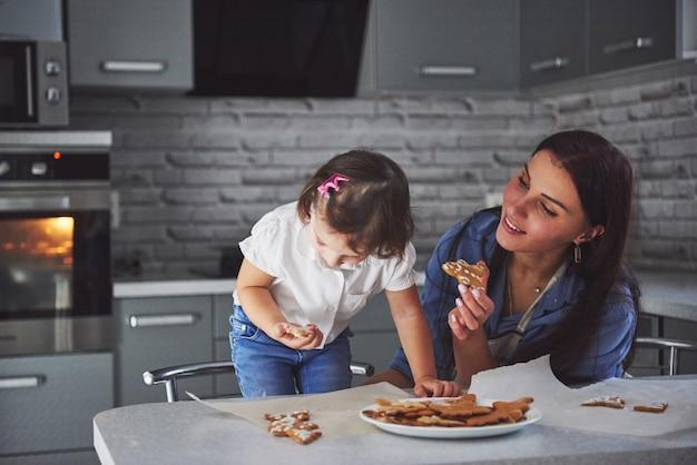 Moeder bak met haar dochter in de keuken. Gratis Foto