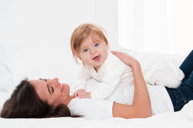 Moeder bedrijf glimlachende baby Gratis Foto