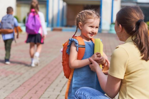 Moeder begeleidt het kind naar school. Premium Foto