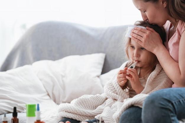 Moeder controleert de temperatuur van haar dochter op een thermometer. medicijnen op tafel. Premium Foto