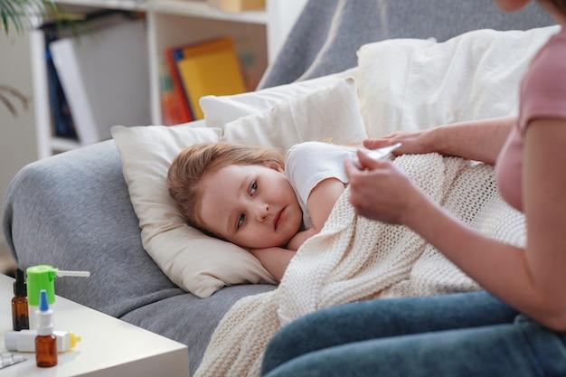 Moeder controleert dochter temperatuur op thermometer. er staan medicijnen op tafel. Premium Foto