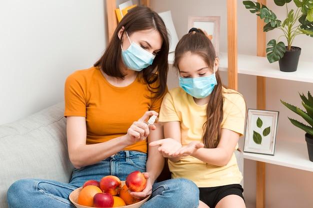 Moeder desinfecteren fruit voor meisje voor het eten Gratis Foto