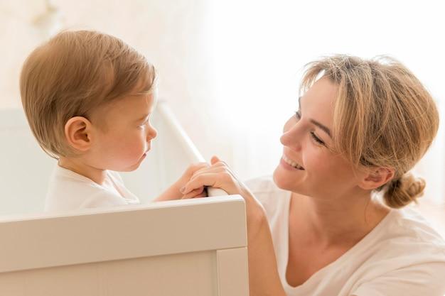 Moeder die bij baby in wieg glimlacht Gratis Foto