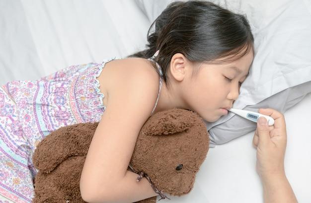 Moeder die de temperatuur van haar zieke jongen meet. Premium Foto