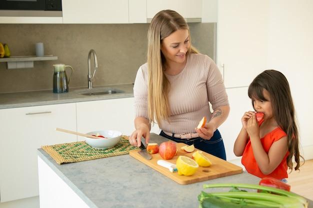 Moeder die dochter geeft om appelschijf te proeven tijdens het koken van salade. meisje en haar moeder samen koken, vers fruit en groenten snijden op snijplank in de keuken. familie koken concept Gratis Foto