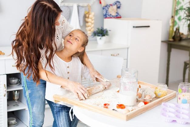 Moeder die dochter onderwijst hoe te keukenrol te gebruiken Gratis Foto