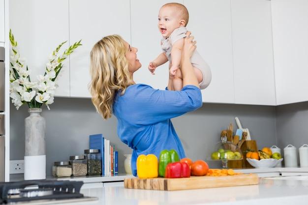 Moeder die haar baby jongen in de keuken foto gratis download