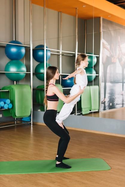 Moeder die haar dochter helpt om oefeningen in gymnastiek te doen Gratis Foto