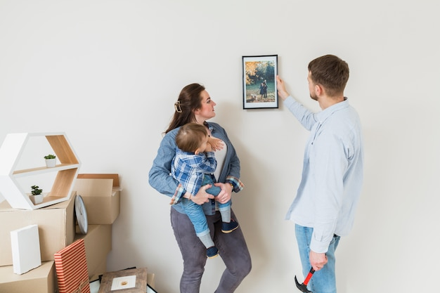 Moeder die haar zoon draagt die frame bekijkt dat door zijn echtgenoot op muur wordt vastgemaakt Gratis Foto
