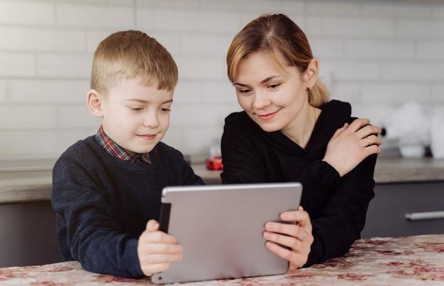 Moeder die laptop en tablet het onderwijs met haar zoon thuis online in zijn ruimte gebruiken Gratis Foto