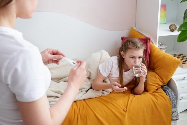 Moeder die medicijnen en een glas water geeft aan haar zieke kind. moeder die zieke dochter vraagt om een pil te nemen Premium Foto