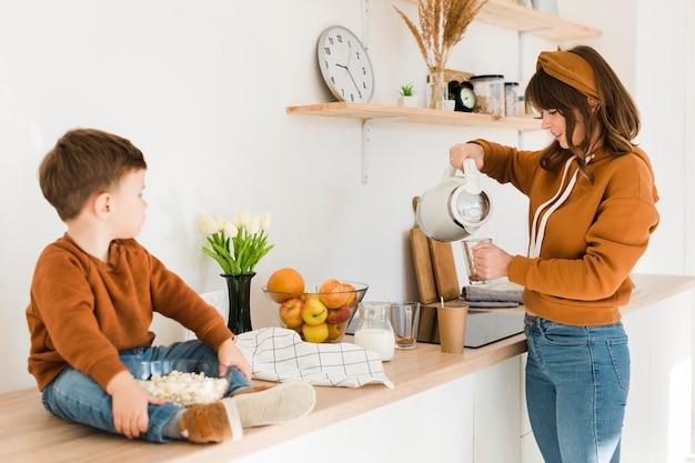 Moeder die melk voor zoon voorbereidt Gratis Foto
