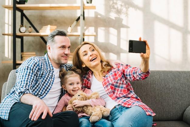 Moeder die selfie van celtelefoon met haar vader en dochter neemt Gratis Foto