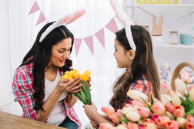 Moeder die van het gele die tulpenboeket houdt door haar dochter op pasen-dag wordt gegeven Gratis Foto