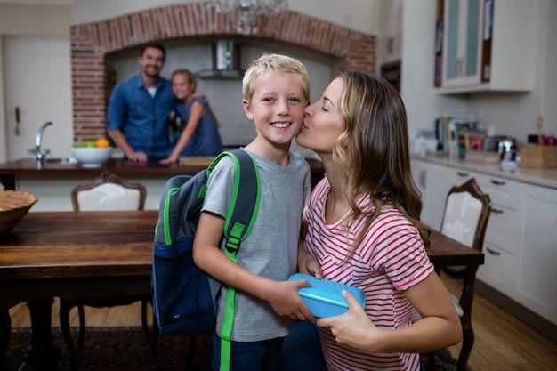Moeder die zijn zoon kust terwijl hij hem een schoolmaaltijddoos geeft Premium Foto