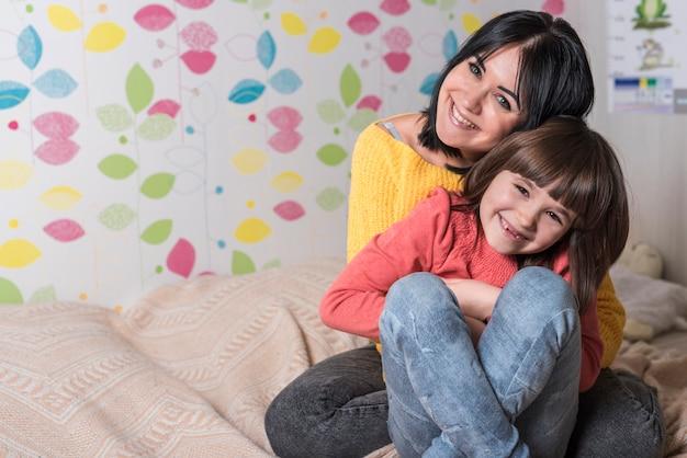 Moeder dochter van achteren knuffelen op bed Gratis Foto