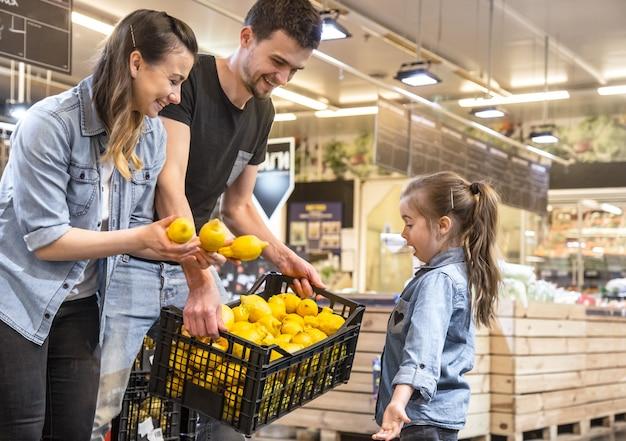 Moeder, echtgenoot en dochter die citroenen in supermarkt kiezen Gratis Foto