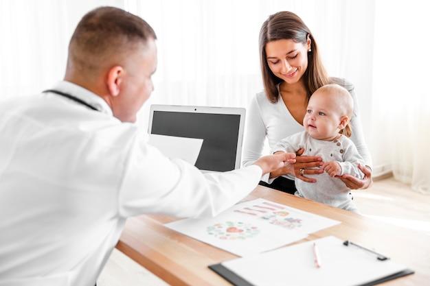 Moeder en arts kijken naar kleine baby Gratis Foto
