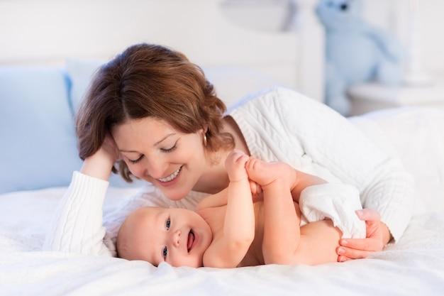 Moeder en baby op een wit bed Premium Foto