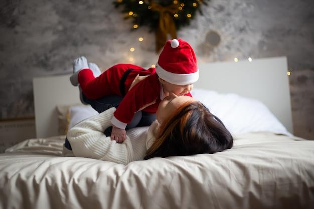Moeder en babyjongen in het kerstmis verfraaide huis Premium Foto