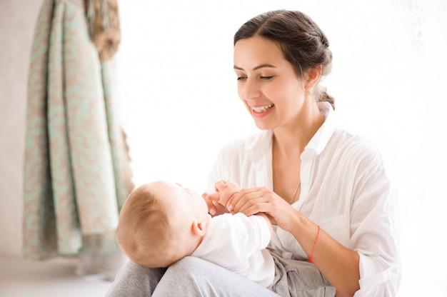 Moeder en babyjongen in luier het spelen in zonnige slaapkamer. familie havi Premium Foto