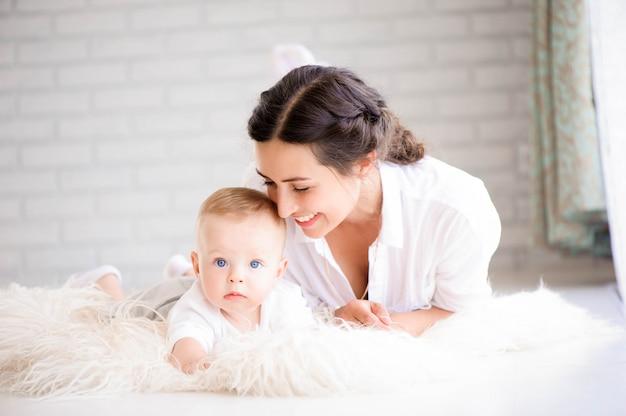 Moeder en babyjongen in luier het spelen in zonnige slaapkamer. Premium Foto