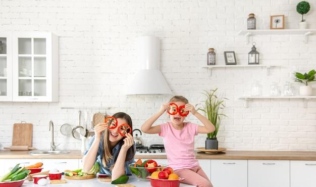 Moeder en dochter bereiden een salade in de keuken. Gratis Foto