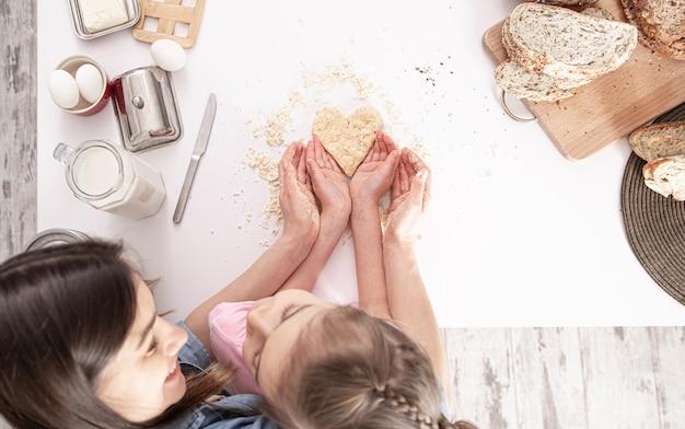 Moeder en dochter bereiden hartvormige koekjes voor op een grote witte keukentafel. Premium Foto