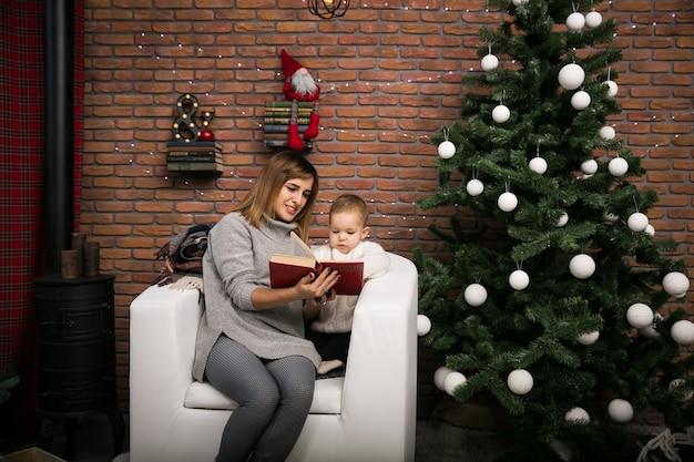 Moeder en dochter bij de kerstboom Gratis Foto