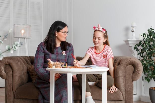 Moeder en dochter brengen samen tijd door, zitten op de bank, praten en tekenen met kleurpotloden Premium Foto