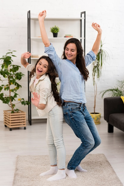 Moeder en dochter dansen in de woonkamer Gratis Foto