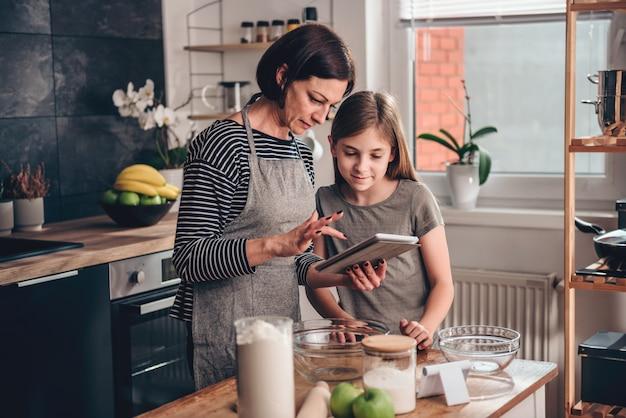 Moeder en dochter die appeltaartrecept zoeken op de tablet Premium Foto