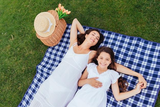 Moeder en dochter die bij picknick ontspannen Gratis Foto