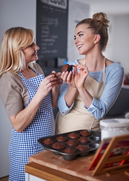 Moeder en dochter die chocolademuffins eten Gratis Foto