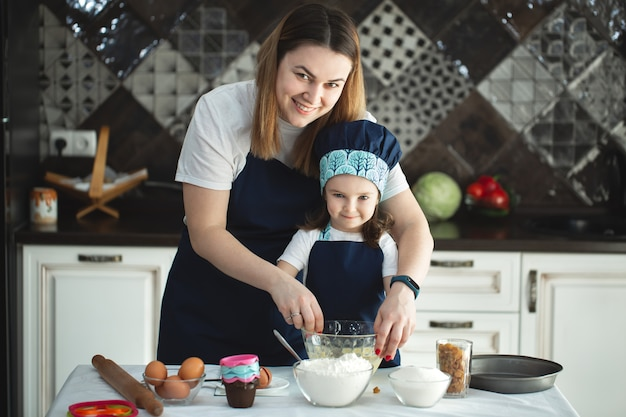 Moeder en dochter die een zoete cake voorbereiden die bloem, melk gebruiken, die op stoelen bij een lijst in een moderne keuken zitten. het meisje houdt zwaait, roert eieren in een kom, bereidend pannekoekdeeg met haar mamma. Premium Foto